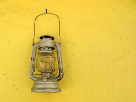 fueled: Lantern old vintage hanging on yellow wall  Stock Photo