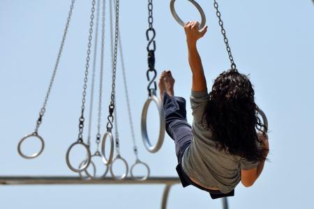 Girl gymnast exercising on rings at Santa Monica Muscle Beach photo