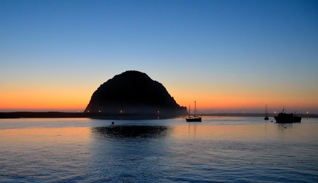 Morro Bay rock and boats in the harbor at dusk photo