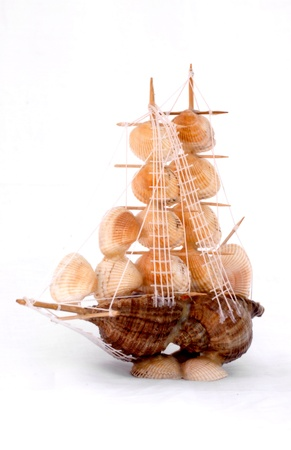 Sailing vessel sea shells and the globe is photographed on a white background photo
