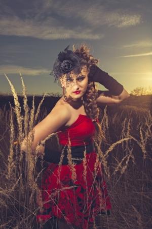 traje de gala: niña en un vestido rojo en la naturaleza
