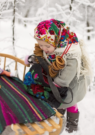little girl with bagels and sled photo