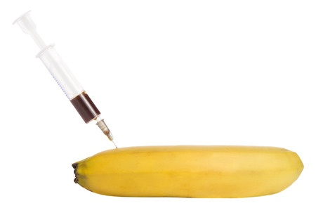 banana with a syringe on a white  photo