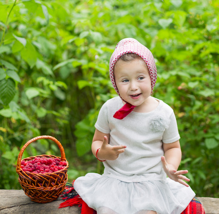 child with a basket of raspberries showing sign of excellent Stock Photo