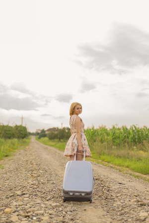 the enchantress: girl with a suitcase outdoors