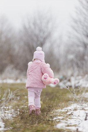 little girl running on the background of a winter park photo