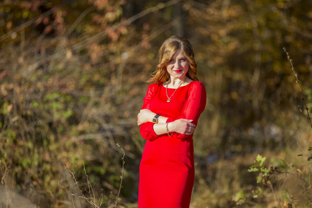 girl in red dress: Girl red dress on a background of yellow foliage Stock Photo