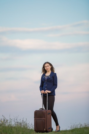 girl with a suitcase against the sky photo