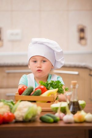 food on table: child cook with vegetables in the kitchen