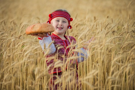 patriotism: Child in Ukrainian national costume with a loaf of bread in her hand Stock Photo