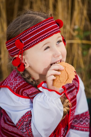 patriotism: Child in Ukrainian national costume with a loaf of bread in his hand