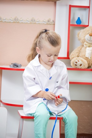 auscultate: Portrait of a child on a background of medical doctors cabinet Stock Photo