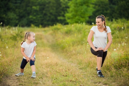 young woman running: child with her mother on the nature train Stock Photo
