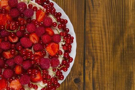 sano: Torta con las fresas y frambuesas grosellas en una mesa de madera