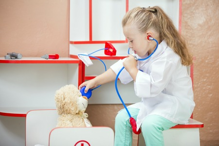 mignonne petite fille: Le médecin de l'enfant examine un ours en peluche