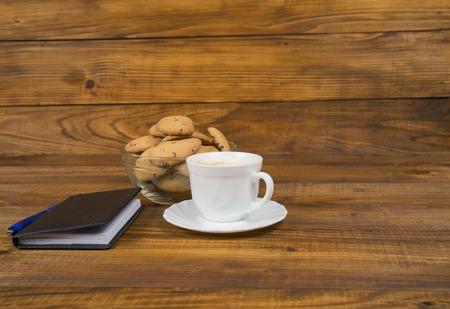 circuito integrado: taza de café y galletas en la mesa de madera