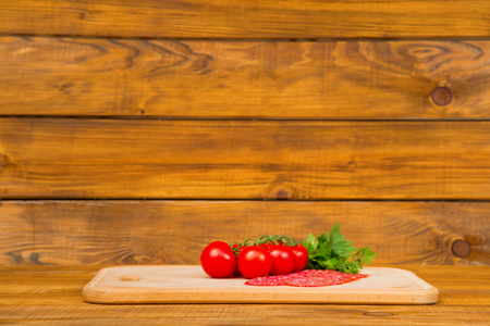 gastronome: tomatoes with sliced sausage on a wooden tray