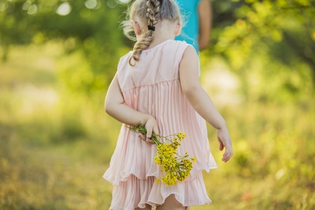 grass: Girl with yellow flowers behind Stock Photo