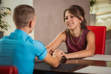 young boys: couple at a table holding hands Stock Photo