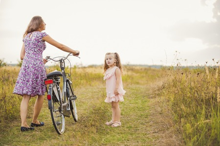 happy family nature: mother with her baby and a bike ride in nature Stock Photo