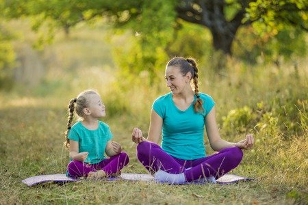 Mom and child in the lotus position on the nature Stock fotó