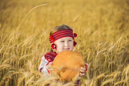 countrified: Child in Ukrainian national costume with a loaf of bread in his hand
