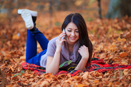 outdoor outside: girl talking on the phone in the autumn park
