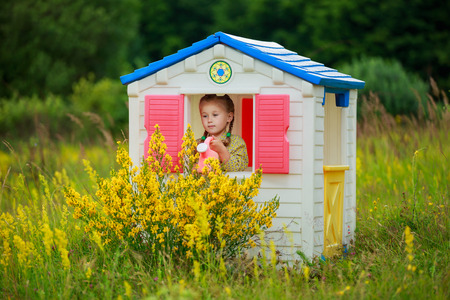 girl in a playhouse in nature