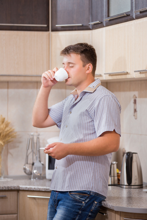 man drinking coffee in the kitchen