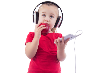 little girl with an apple and a phone with headphones on white background