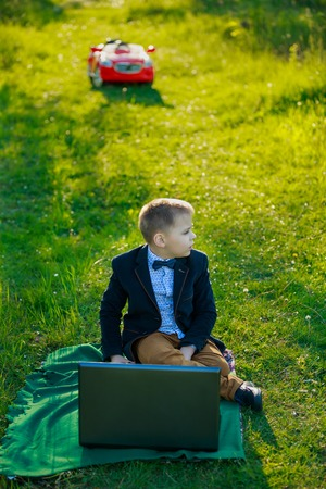boy with a laptop on nature