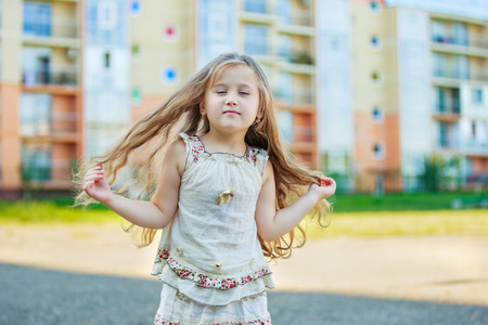 little girl with long hair on a background of a modern apartment building