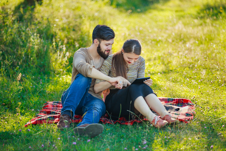 happy couple with a tablet in nature Stock fotó