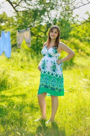 Pregnant woman hanging laundry outdoors Stock fotó