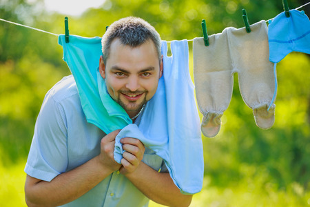man near the childrens clothing hanging on a rope outdoors