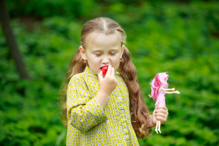 little girl eating a strawberry on the nature Stock fotó