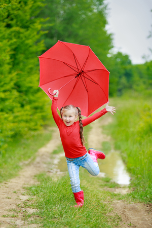 rain wet: little girl with a red umbrella on the nature