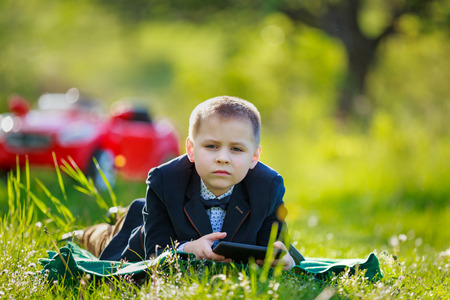 boy with tablet lying on the lawn Stock fotó