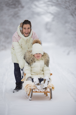 Mom rolls her daughter on a sled in winter park Stock fotó