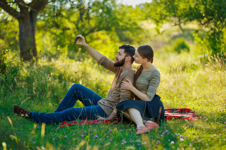 happy couple with phone in nature