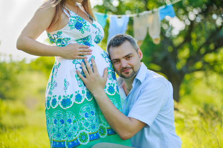 Happy expectant father listening to the belly of his pregnant wife on the nature Stock fotó