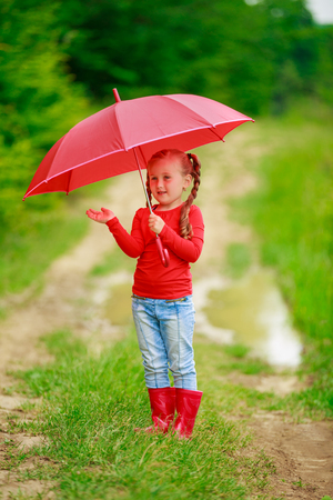little girl with a red umbrella on the nature