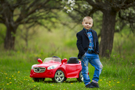 young man in the park against the backdrop of a red car Stock fotó