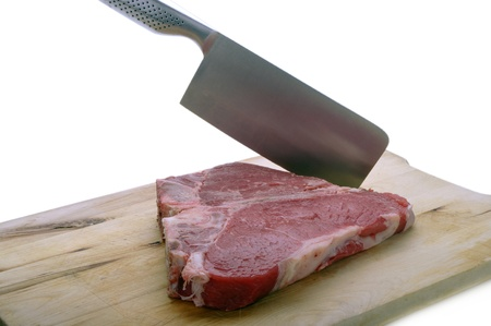 Florentine steak on wooden chopping board with cleaver photo