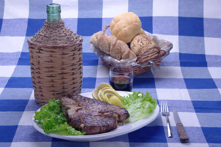 florentine: ablecloth rustic Florentine steak bottle of wine and bread basket Stock Photo