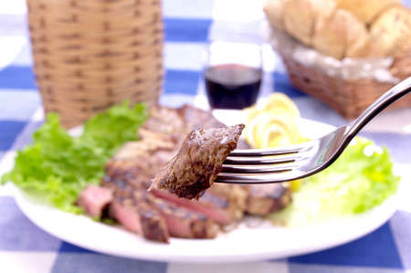 morsel: fork with morsel of meat on a plate with Florentine steak Stock Photo