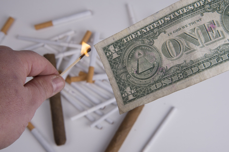 Flame and dollar with cigarettes and cigars background Stock Photo