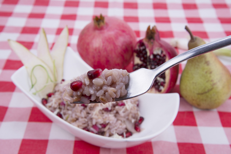 forkful of risotto with pears and pomegranate