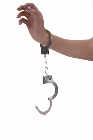 handcuffs: womans hand with handcuffs on white background Stock Photo