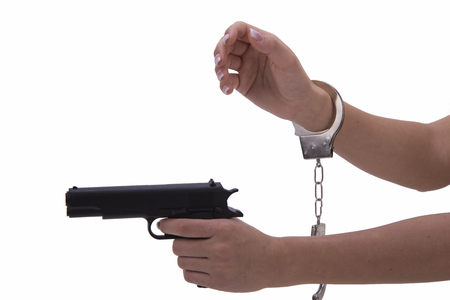 denunciation: womans hand with handcuffs and gun on a white background Stock Photo